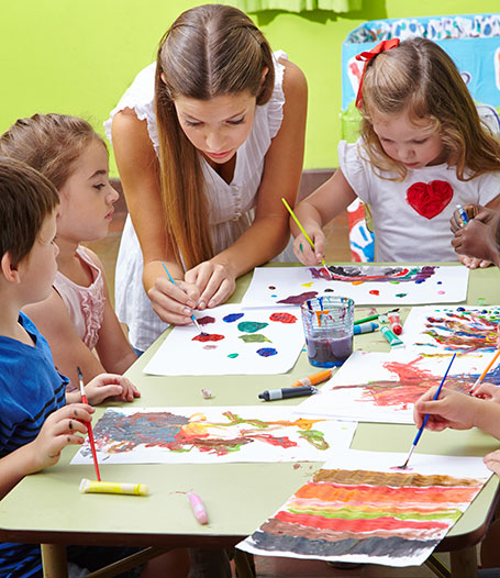Nursery teacher painting with children and brushes and watercolor in kindergarten