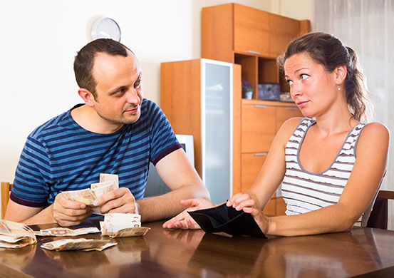 Young woman and her husband counting budget for a month